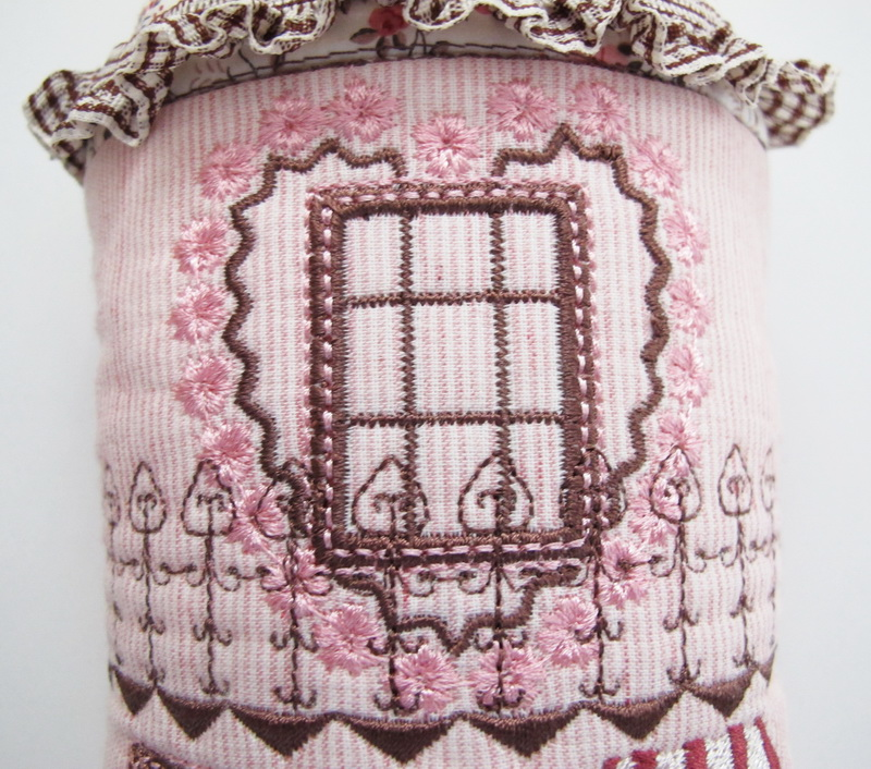 Country Chic Machine Embroidery Designs by Stitchingart. Door hanging, country style with house, windows, fencing, flowers in pot.